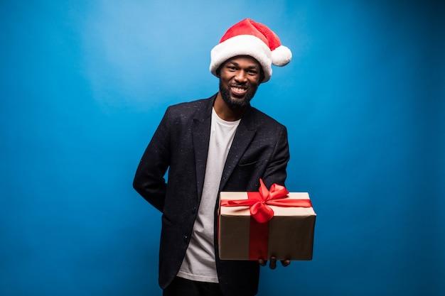 Jovem afro-americano com chapéu de papai noel e oferecendo um presente