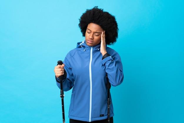 Jovem afro-americano com mochila e bastões de trekking isolados em azul com dor de cabeça