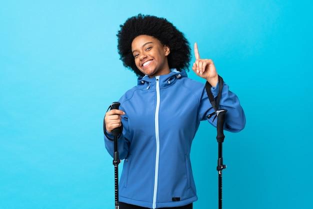 Jovem afro-americano com mochila e bastões de trekking isolados em azul mostrando e levantando um dedo em sinal dos melhores