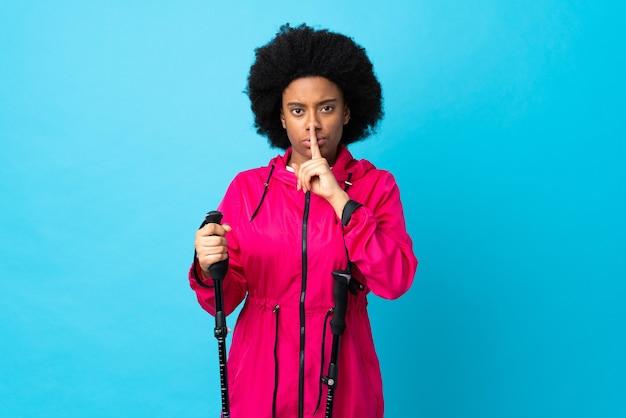 Jovem afro-americano com mochila e bastões de trekking isolados em azul mostrando sinal de silêncio gesto de colocar o dedo na boca