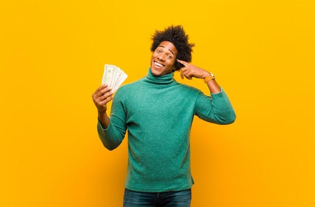 Jovem afro-americano com notas de dólar nas costas laranja