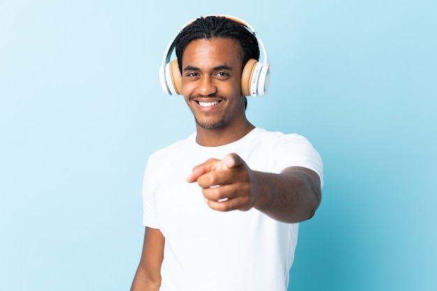 Jovem afro-americano com tranças em azul ouvindo música e apontando para a frente