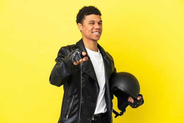Jovem afro-americano com um capacete de motociclista isolado em um fundo amarelo apontando para a frente com uma expressão feliz
