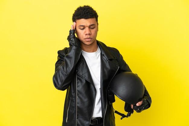 Jovem afro-americano com um capacete de motociclista isolado em um fundo amarelo com dor de cabeça