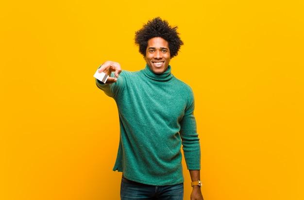 Jovem afro-americano com um cartão de crédito contra bac laranja