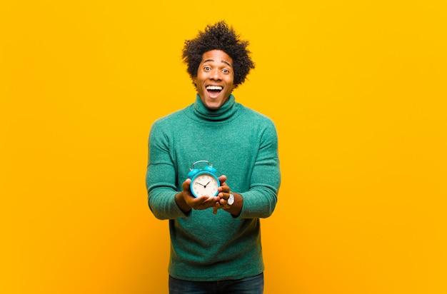 Jovem afro-americano com um despertador contra laranja ba