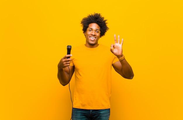 Jovem afro-americano com um microfone cantando contra ou
