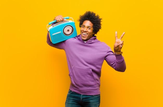 Jovem afro-americano com um rádio vintage contra laranja b