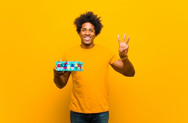 Jovem afro-americano com uma caixa de presente contra uma parede laranja