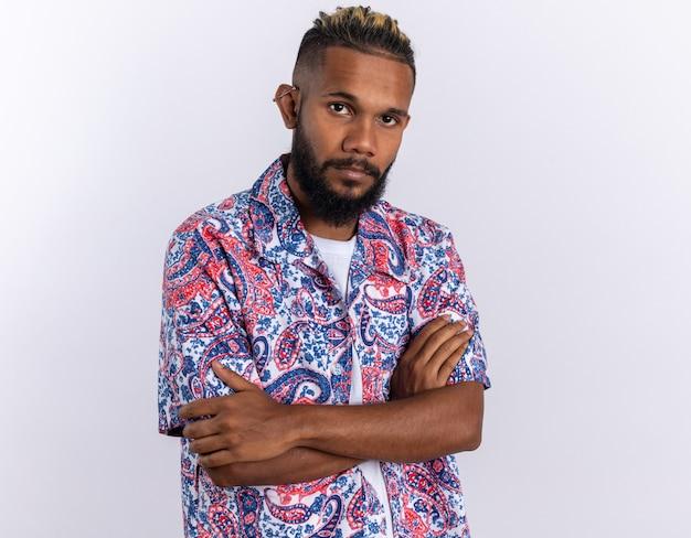 Jovem afro-americano com uma camisa colorida, olhando para a câmera com uma cara séria