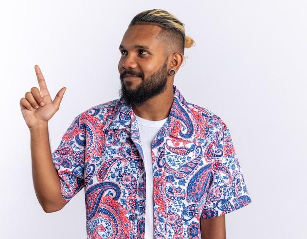 Jovem afro-americano com uma camisa colorida olhando para o lado sorrindo alegremente apontando com o dedo indicador para o lado em pé sobre um fundo branco