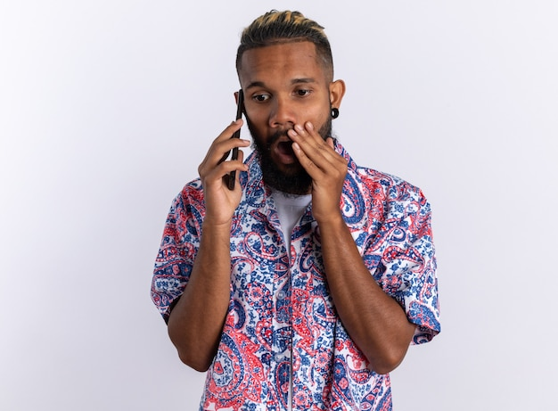 Jovem afro-americano com uma camisa colorida parecendo surpreso e chocado enquanto fala ao celular em pé sobre o branco