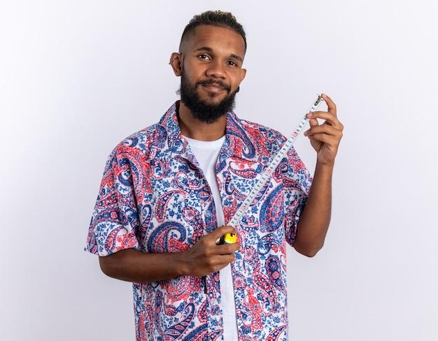 Jovem afro-americano com uma camisa colorida segurando uma fita métrica, olhando para a câmera com um sorriso no rosto feliz e positivo em pé sobre um fundo branco