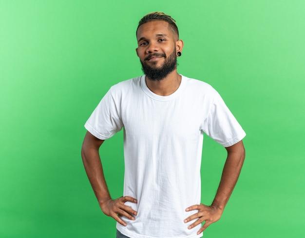 Jovem afro-americano com uma camiseta branca olhando para a câmera com um sorriso no rosto e os braços na altura do quadril em pé sobre um fundo verde