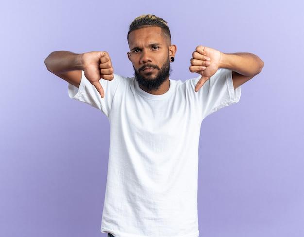 Jovem afro-americano com uma camiseta branca olhando para a câmera com uma cara séria apontando com os dedos indicadores para baixo em pé sobre um fundo azul