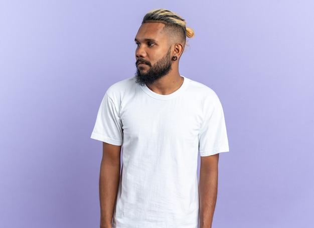 Jovem afro-americano com uma camiseta branca olhando para o lado com uma cara séria em pé sobre um fundo azul