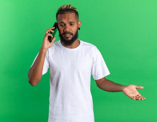 Jovem afro-americano com uma camiseta branca parecendo confuso enquanto fala no celular