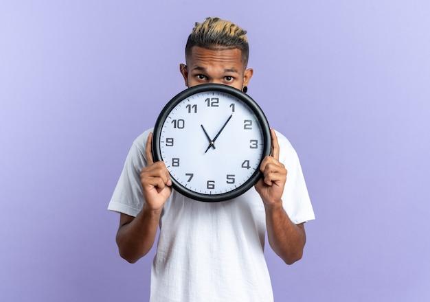 Jovem afro-americano com uma camiseta branca segurando um relógio de parede na frente do rosto preocupado