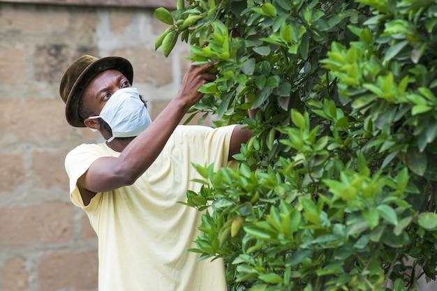 Jovem afro-americano com uma máscara protetora trabalhando em seu jardim