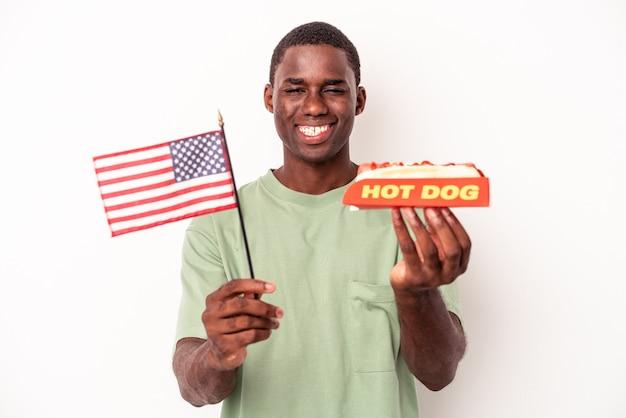 Jovem afro-americano comendo cachorro-quente e segurando a bandeira americana isolada no fundo branco