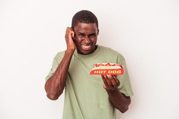 Jovem afro-americano comendo um cachorro-quente isolado no fundo branco, cobrindo as orelhas com as mãos.
