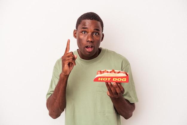 Jovem afro-americano comendo um cachorro-quente isolado no fundo branco, tendo uma ideia, o conceito de inspiração.