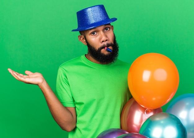 Jovem afro-americano confuso usando chapéu de festa soprando apito de festa estendendo a mão