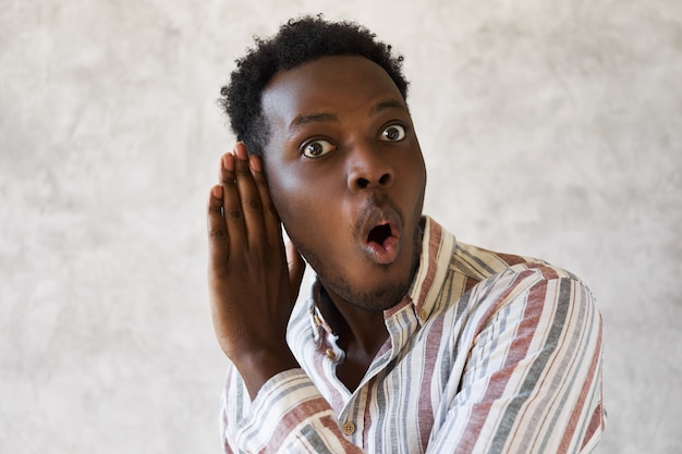 Jovem afro-americano curioso e emocional com a boca escancarada expressando surpresa e total descrença segurando a mão em seu ouvido ouvindo uma conversa particular secreta, ficando totalmente chocado
