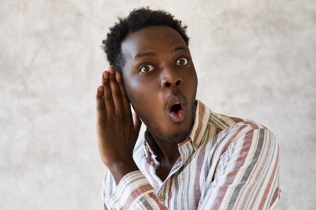 Jovem afro-americano curioso e emocional com a boca escancarada expressando surpresa e total descrença, segurando a mão em seu ouvido, ouvindo uma conversa particular secreta