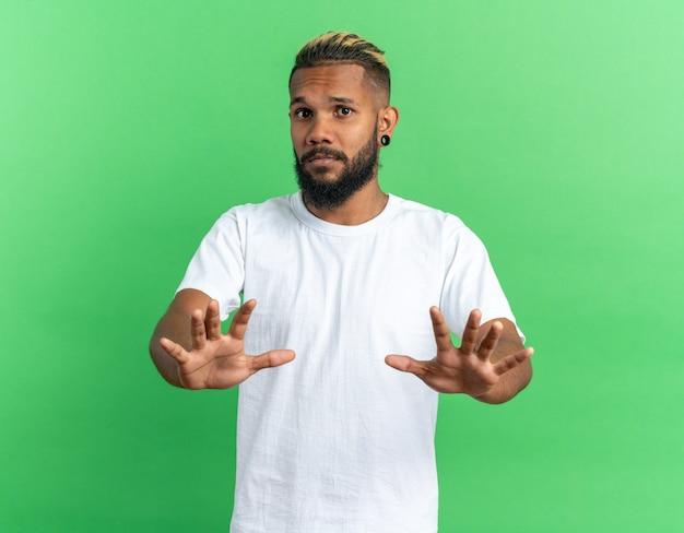 Jovem afro-americano de camiseta branca olhando para a câmera assustado de mãos dadas fazendo gesto de defesa