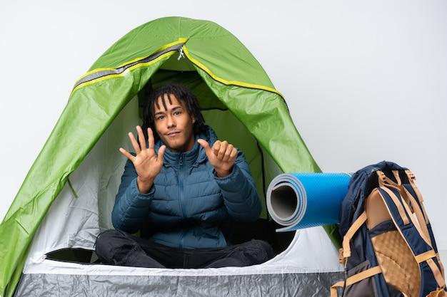 Jovem afro-americano dentro de uma barraca de acampamento verde, contando seis com os dedos