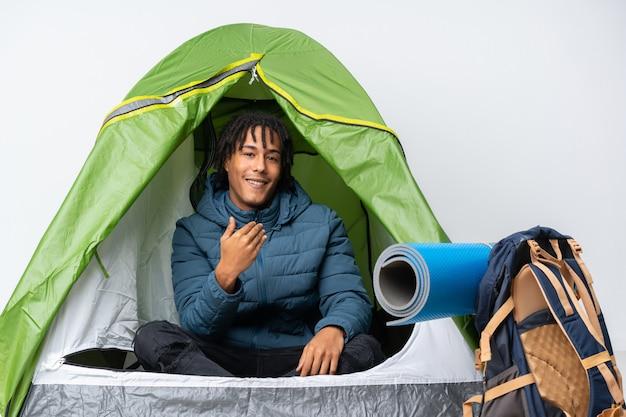 Jovem afro-americano dentro de uma barraca de acampamento verde, convidando para vir com a mão
