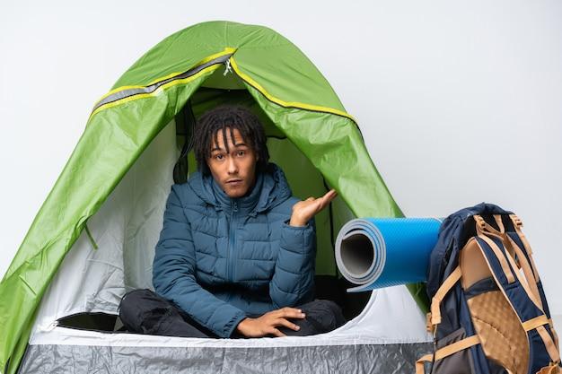 Jovem afro-americano dentro de uma barraca de acampamento verde, fazendo o gesto de dúvidas