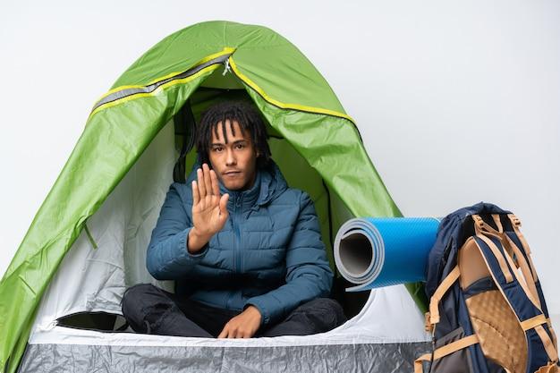 Jovem afro-americano dentro de uma barraca de acampamento verde, fazendo o gesto de parada