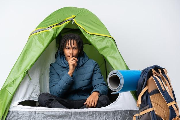 Jovem afro-americano dentro de uma barraca de acampamento verde, mostrando um sinal de gesto de silêncio colocando o dedo na boca