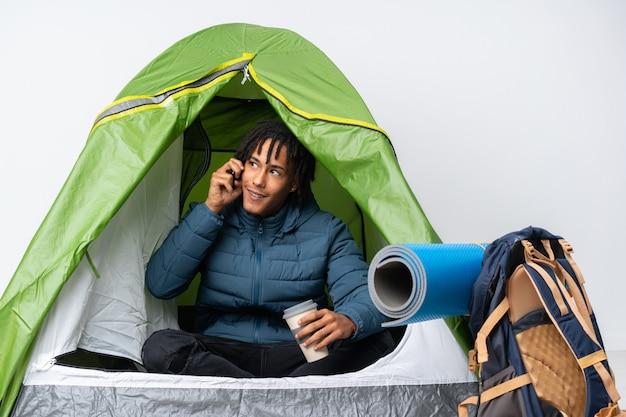 Jovem afro-americano dentro de uma barraca de acampamento verde segurando café para tirar e um celular