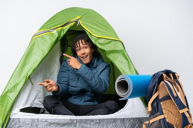 Jovem afro-americano dentro de uma barraca de acampamento verde surpreso e apontando o lado