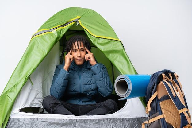 Jovem afro-americano dentro de uma barraca de acampamento verde tendo dúvidas e pensando