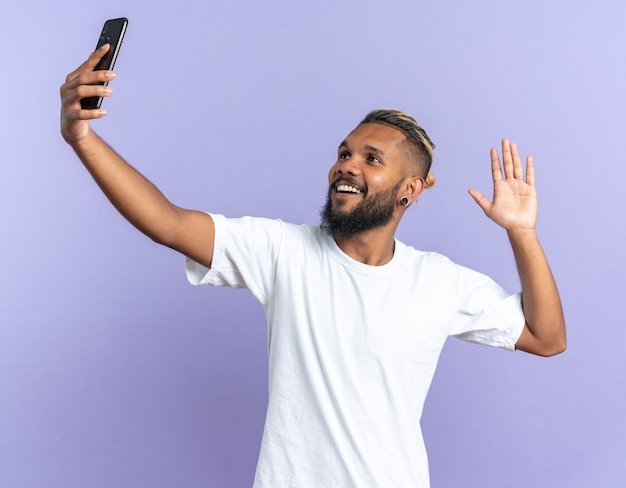 Jovem afro-americano em camiseta branca fazendo selfie usando smartphone feliz e alegre sorrindo acenando com a mão