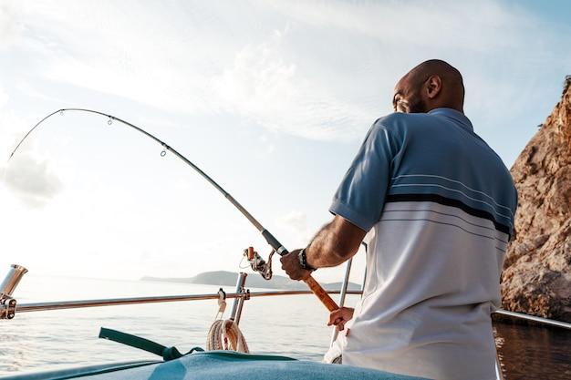 Jovem afro-americano em pé com a vara de pescar em um veleiro, pescando em mar aberto, ao pôr do sol