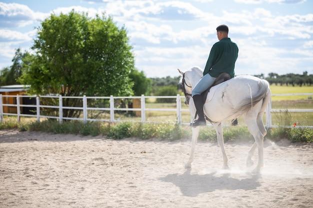 Jovem afro-americano em roupa casual, andar a cavalo branco no chão arenoso no rancho
