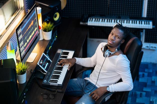 Jovem afro-americano em trajes casuais olhando para você sentado no local de trabalho em um estúdio de gravação de som enquanto trabalha