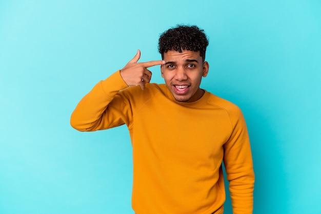 Jovem afro-americano encaracolado isolado em azul, mostrando um gesto de decepção com o dedo indicador.