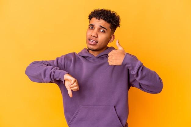 Jovem afro-americano encaracolado isolado em roxo, mostrando os polegares para cima e os polegares para baixo, é difícil escolher o conceito