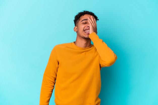 Jovem afro-americano encaracolado isolado no azul, rindo de emoção feliz, despreocupada e natural.