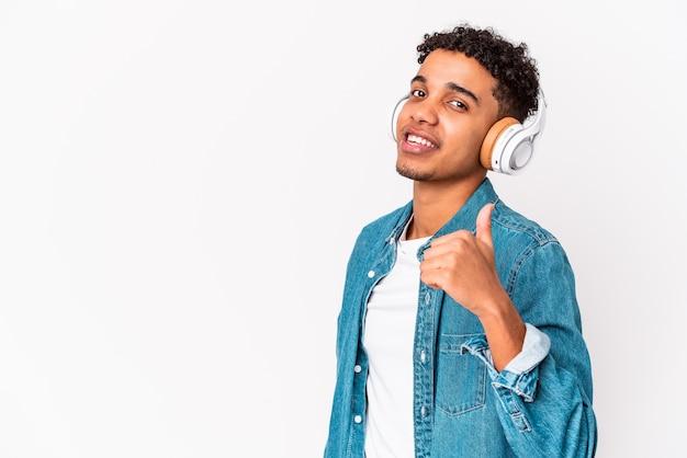 Jovem afro-americano encaracolado isolado ouvindo música com fones de ouvido sorrindo e levantando o polegar