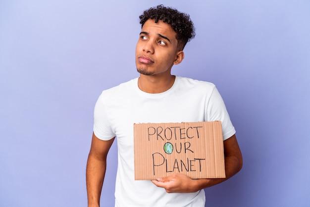 Jovem afro-americano encaracolado isolado segurando um proteger nosso planeta confuso, sente-se duvidoso e inseguro.