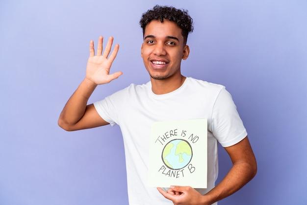 Jovem afro-americano encaracolado isolado segurando um theres é nenhum cartaz do planeta b sorrindo alegre mostrando o número cinco com os dedos.