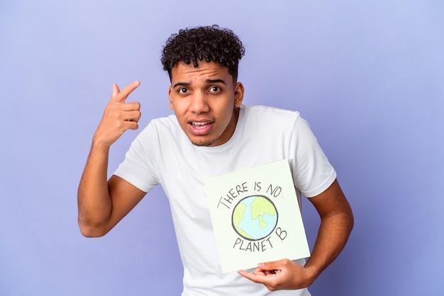 Jovem afro-americano encaracolado isolado segurando um theres há nenhum cartaz do planeta b mostrando um gesto de decepção com o dedo indicador.
