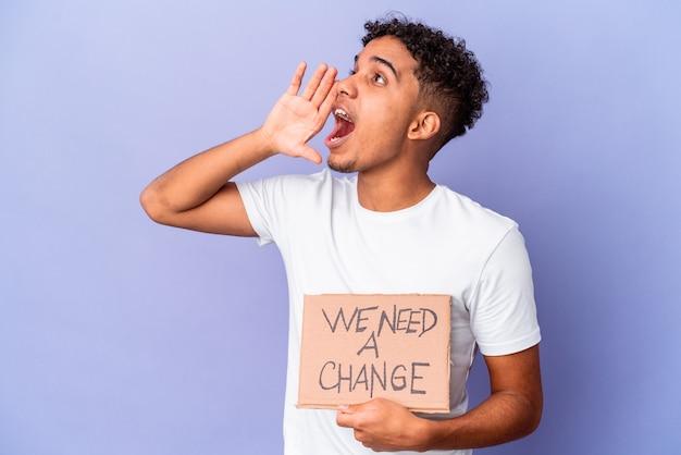 Jovem afro-americano encaracolado segurando um papelão de precisamos de uma mudança